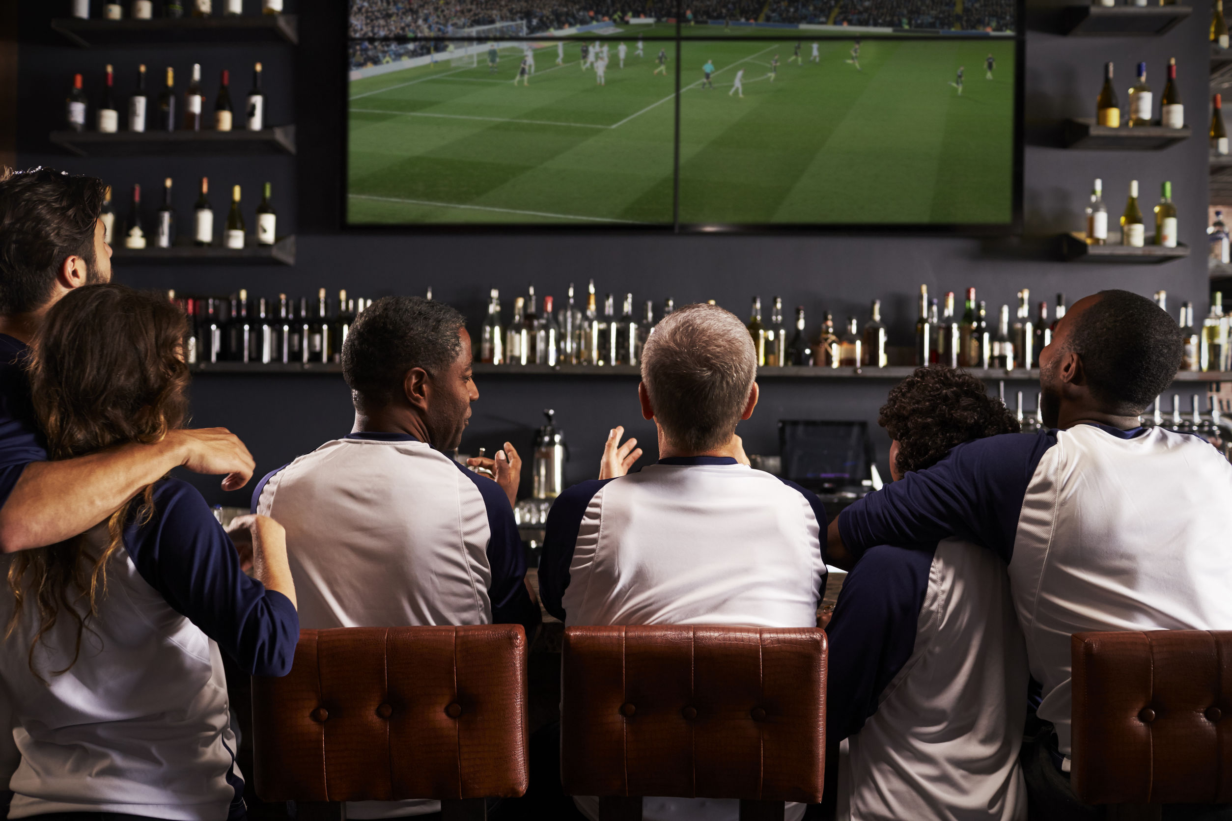 Satellite TV Rear View Of Friends Watching Game In Sports Bar Celebrating